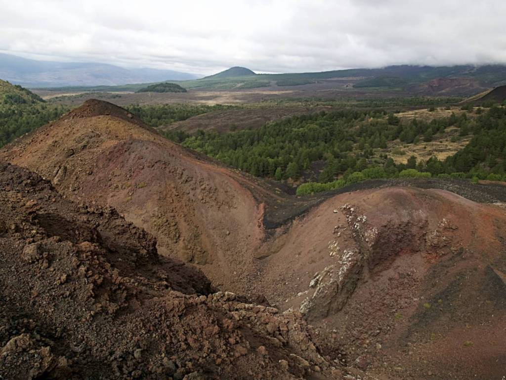 Panorama etneo con terra rossiccia. Sullo sfondo zona verdeggiante