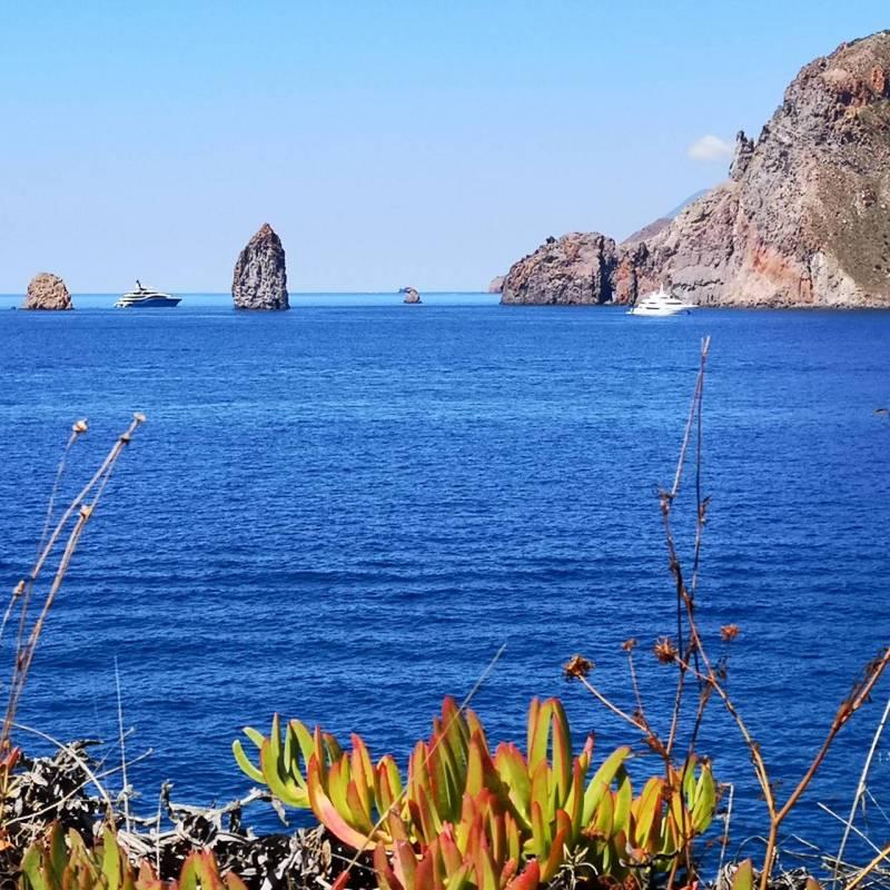 Vista dei faraglioni delle isole Eolie con barche e aliscafi in transito