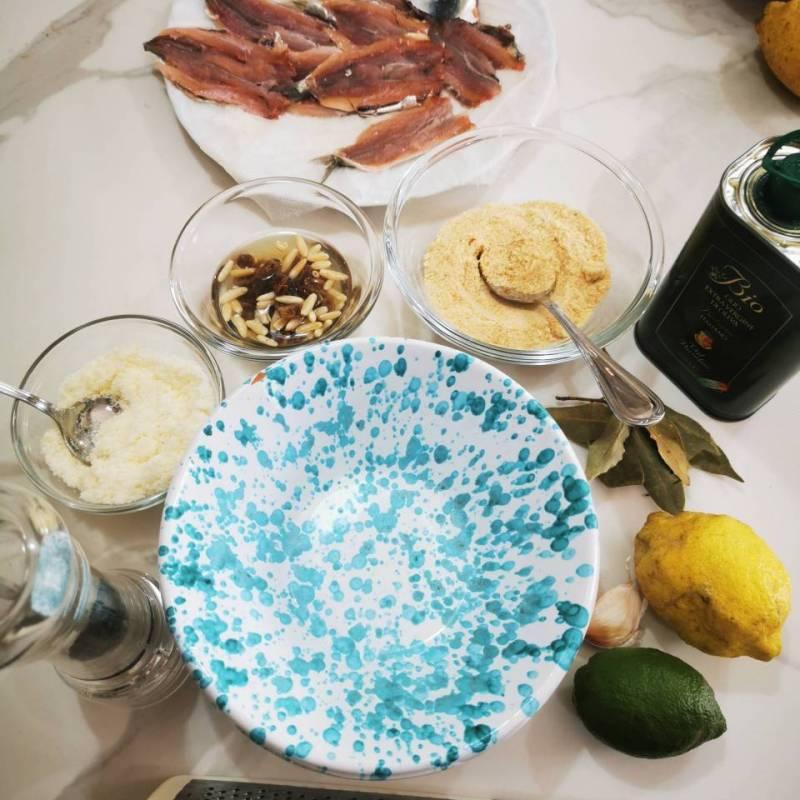 Esposizione ingredienti: olio, limone, parmigiano, pan grattato, pepe, aglio, pinoli, uva sultanina, alloro, alici