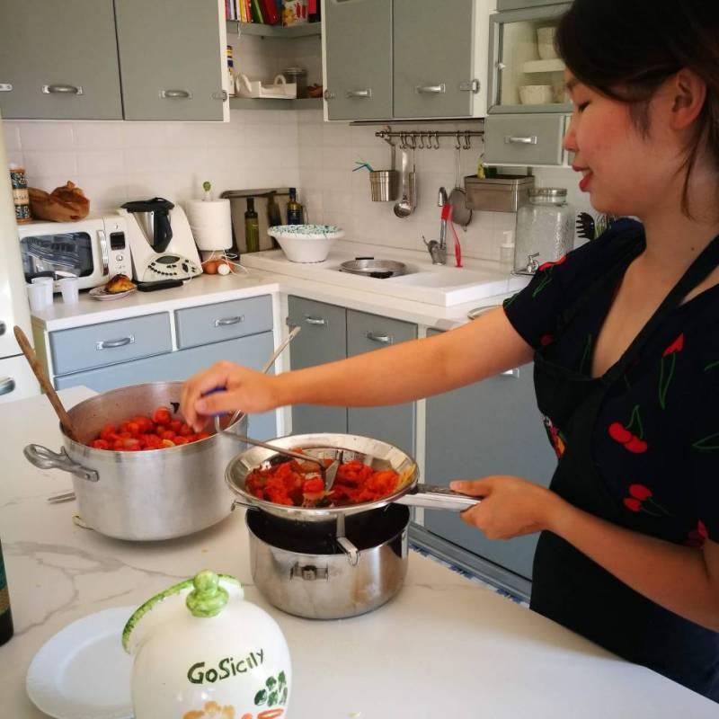Donna asiatica che setaccia i pomodori