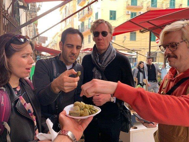 Turisti che degustano lo street food al mercato di Palermo