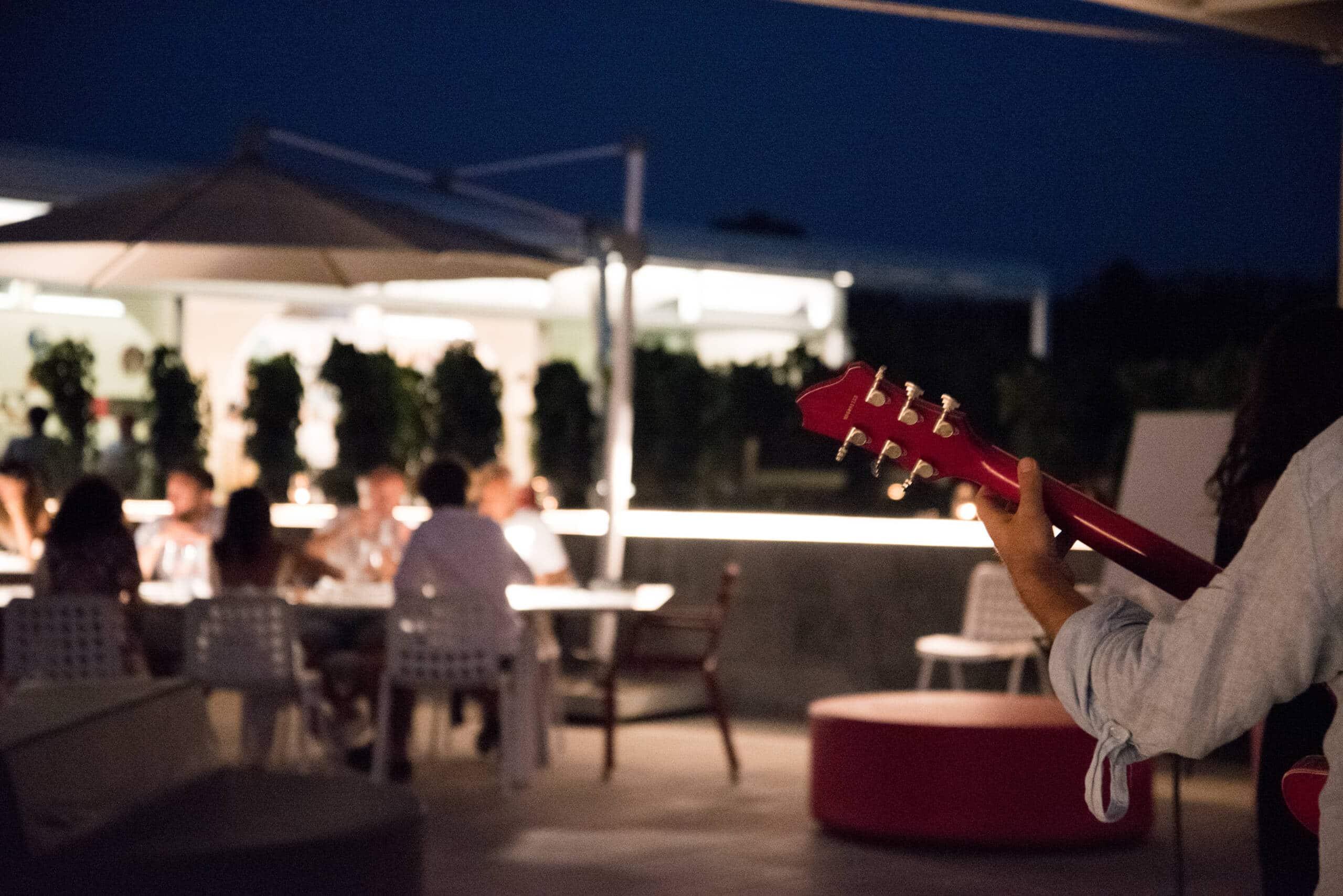 Finale chitarra con gruppo di persone in lontananza