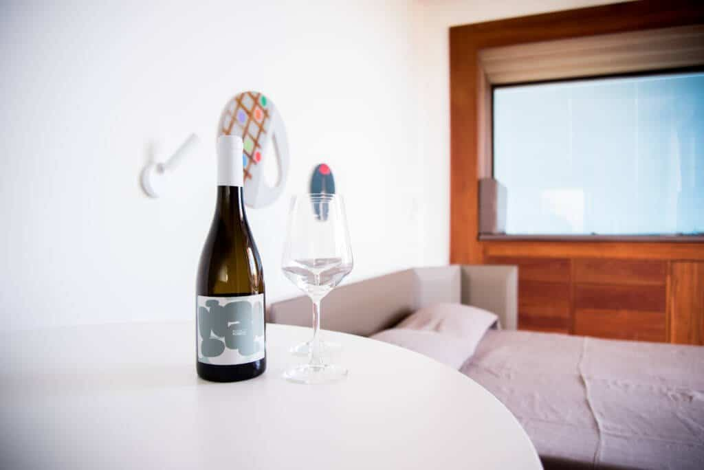 Bottiglia di vino con calice, in camera
