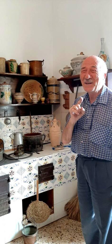 Artigiano di Caltagirone che racconta la storia della cucina che ha in casa con suppellettili