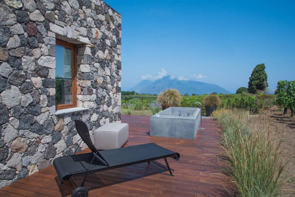 Esterno camera con vasca, lettino, con sfondo isole e vigneto