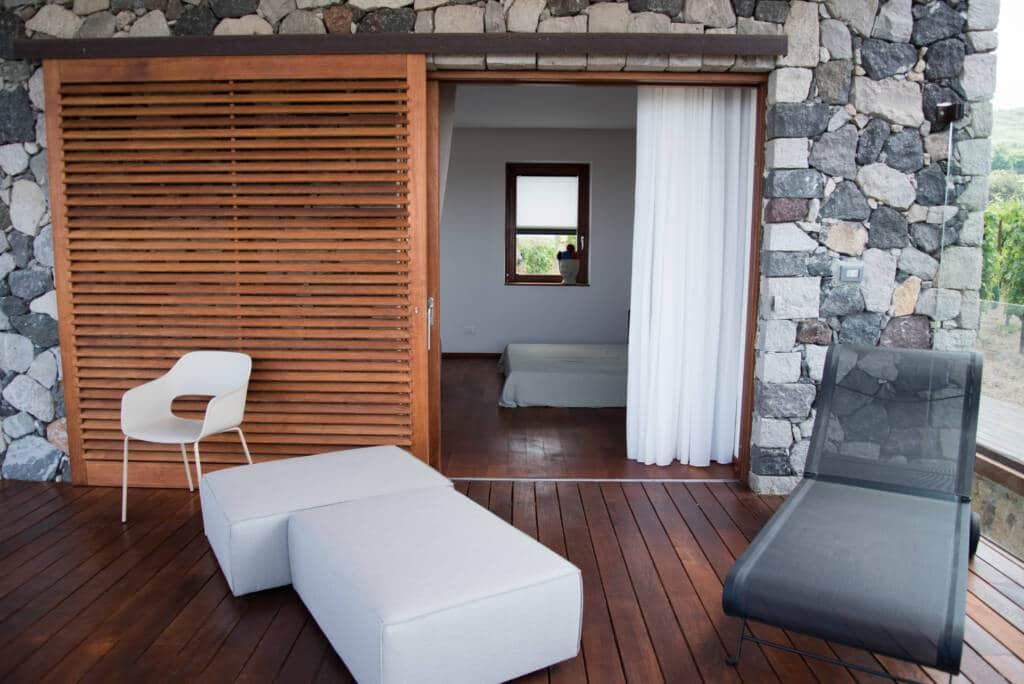 Vista dall'esterno camera, divanetto e lettino sul patio