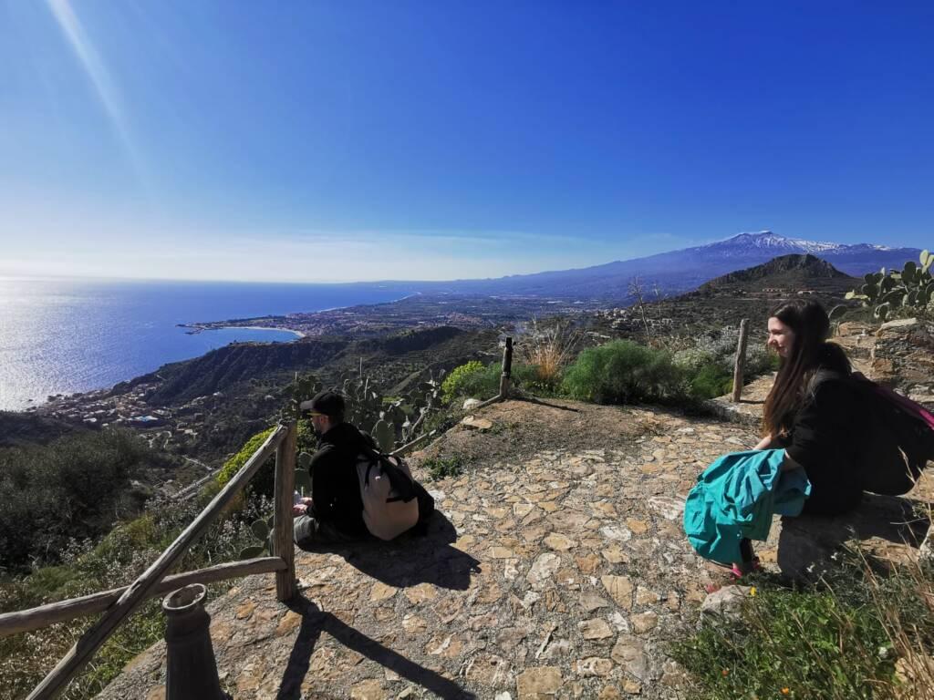 Trekkisti seduti che guardano il mare con sfondo Etna