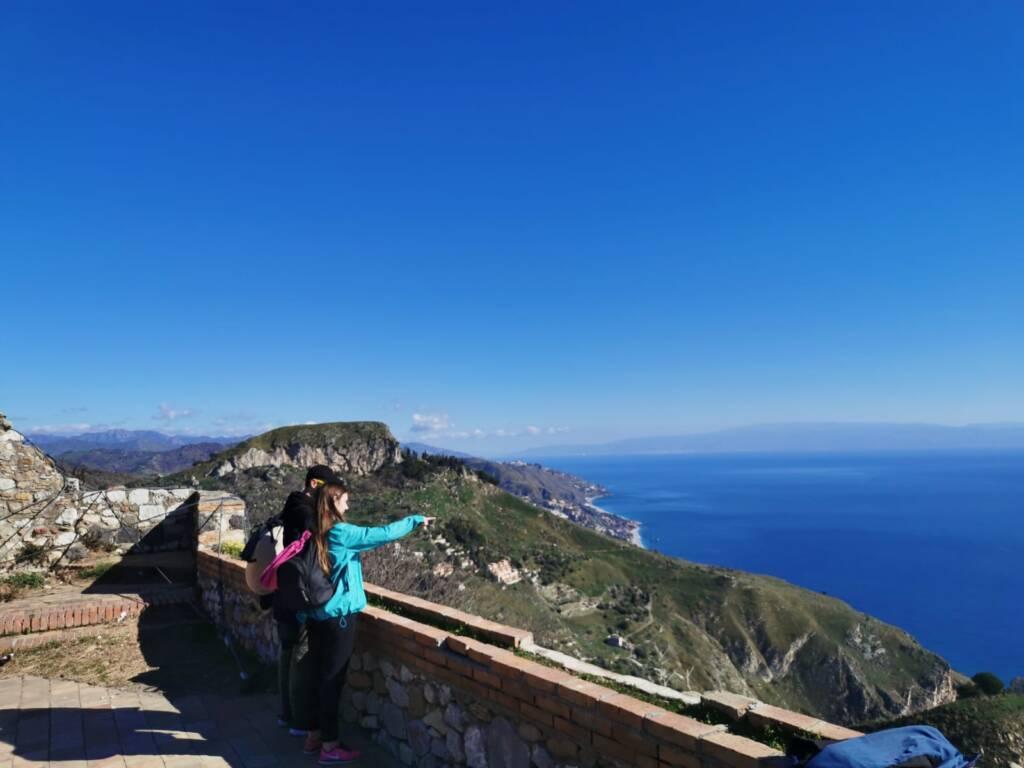 Trekkisti che indicano il mare dal terrazzo da Taormina