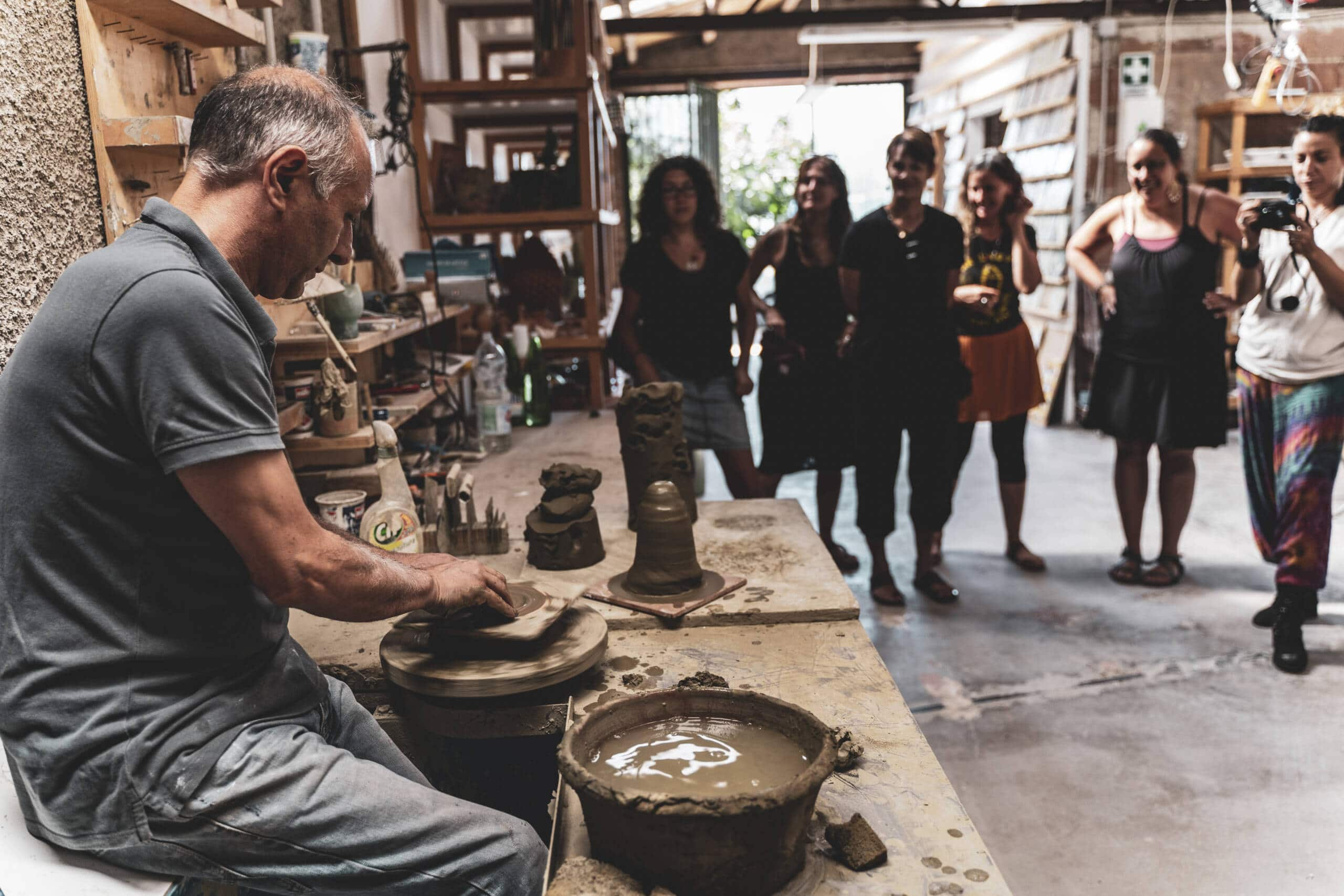 Uomo seduto che dimostra l'utilizzo del tornio e l'argilla