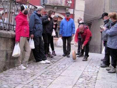 Gruppo di persone che fa ruotare il Maiorchino, formaggio tipico di Novara di Sicilia