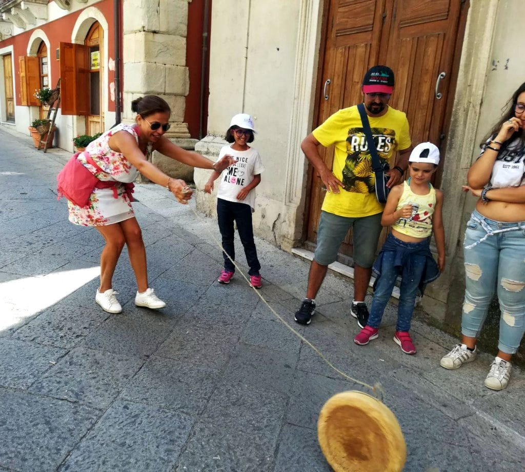 Gruppo di persone che prova a far rotolare il maiorchino, formaggio tipico di Novara di Sicilia