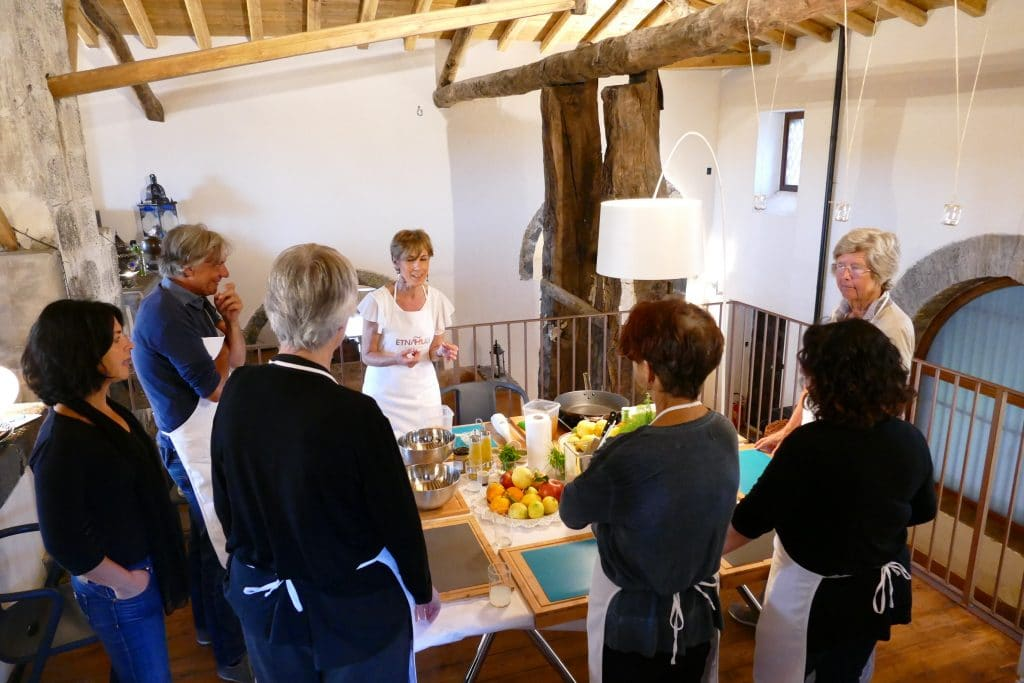 Partecipanti ad una cooking class attorno ad un tavolo