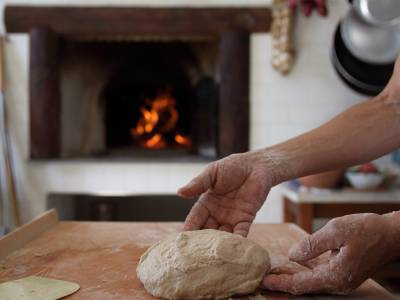 mani di donna che impastano il pane e fuoco acceso