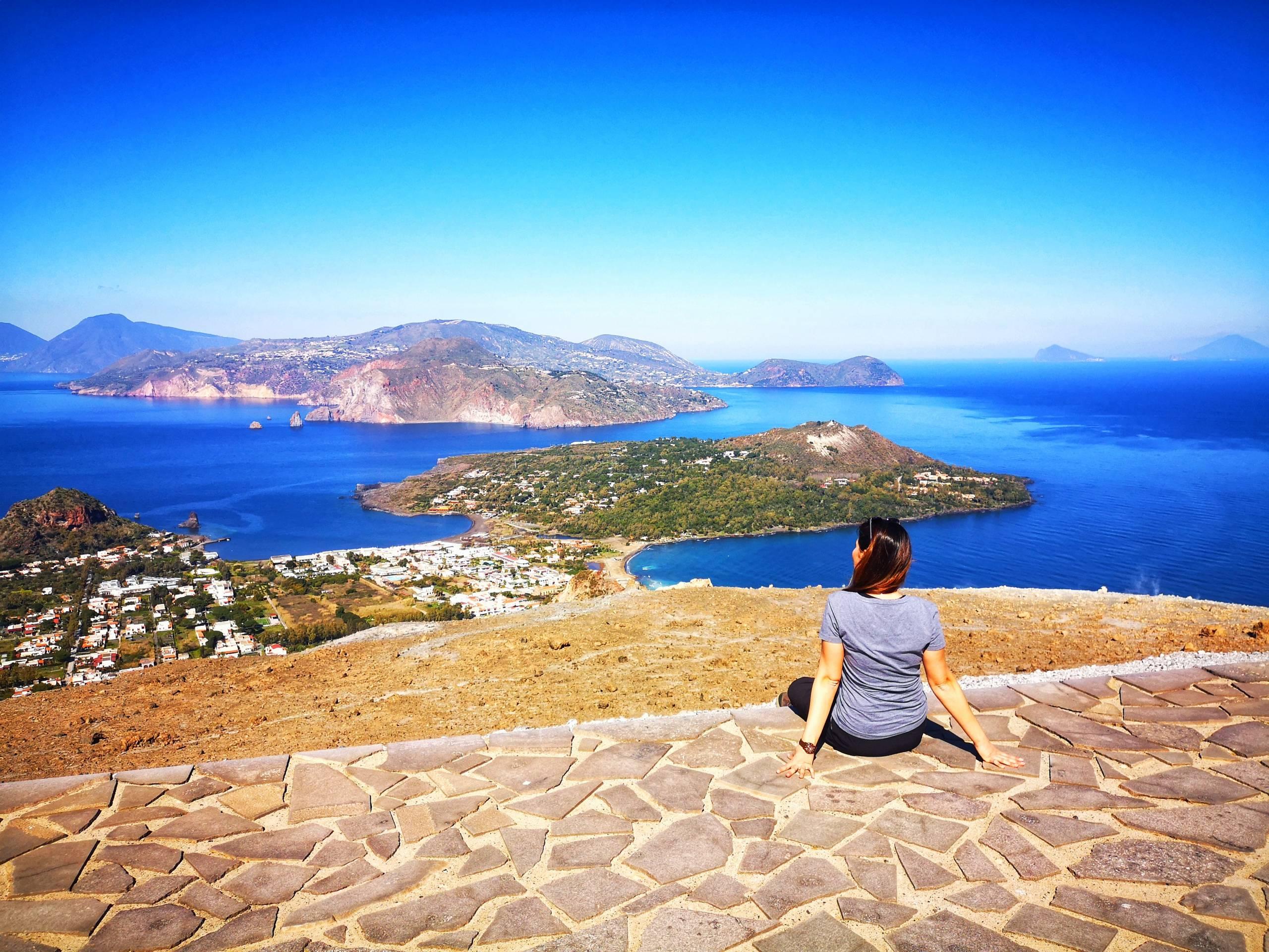 Guida seduta su un promontorio mentre ammira il panorama e le isole vicine