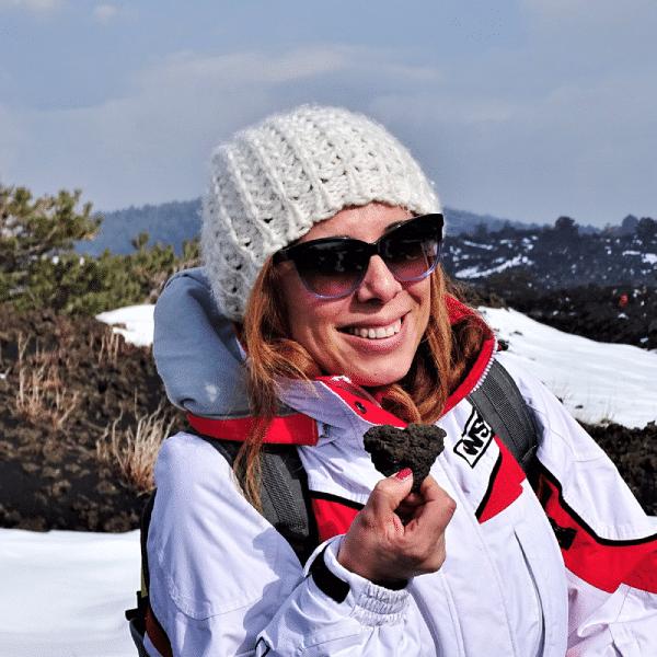 Isolana Patrizia con un cuore di pietra lavica sull'Etna innevata